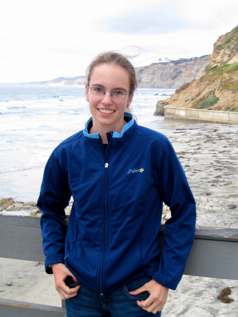 Image is of Elizabeth Sibert, a white woman with glasses and a ponytail wearing a blue zip-up jacket. She is leaning on the railing of Scripps Pier with her back to a beach and ocean in the background.
